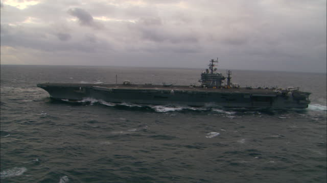 an aircraft carrier glides in the ocean. - kriegsschiff stock-videos und b-roll-filmmaterial