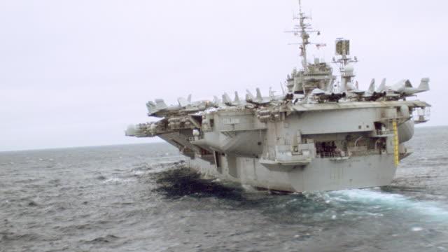 an aircraft carrier leads a naval flotilla. - flugzeugträger stock-videos und b-roll-filmmaterial