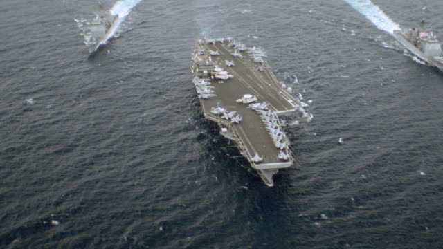 an aircraft carrier leads a naval strike force. - flotilla stock videos & royalty-free footage
