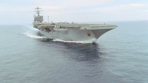 an aircraft carrier leaves a large wake as it travels on the ocean. - warship stock videos & royalty-free footage