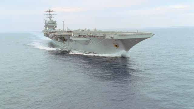 an aircraft carrier leaves a large wake as it travels on the ocean. - aircraft carrier stock videos & royalty-free footage