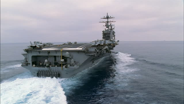 an aircraft carrier moves quickly in the ocean. - aircraft carrier stock videos & royalty-free footage