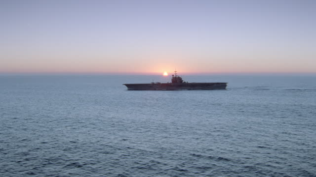 vidéos et rushes de an aircraft carrier travels over the ocean against a pink and blue sky. - aller tranquillement