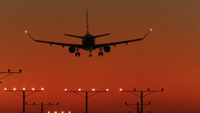vídeos de stock, filmes e b-roll de ls an aircraft comes in to land at sunset / los angeles, usa - aterrissando