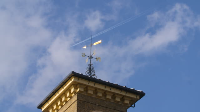 An aircraft flies over the clock tower on top of Kings Cross Station, London.