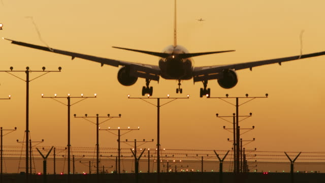 LS An aircraft lands on a runway at sunset / Los Angeles, USA