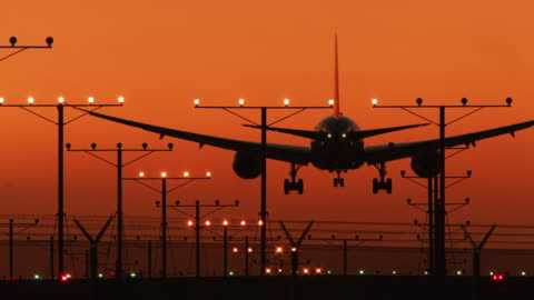 ls an aircraft lands on a runway at sunset / los angeles, usa - image stock-videos und b-roll-filmmaterial