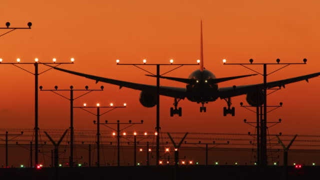 ls an aircraft lands on a runway at sunset / los angeles, usa - air vehicle stock-videos und b-roll-filmmaterial