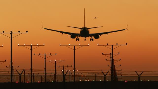 LS, SLO MO An aircraft lands on a runway at sunset / Los Angeles, USA