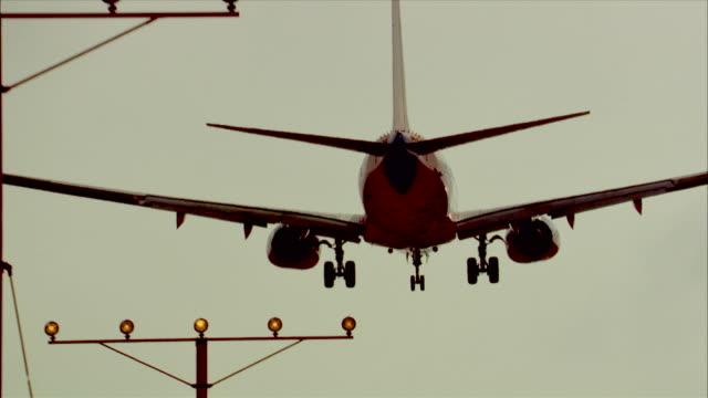 an airliner lands at los angeles international airport. - landefahrwerk stock-videos und b-roll-filmmaterial