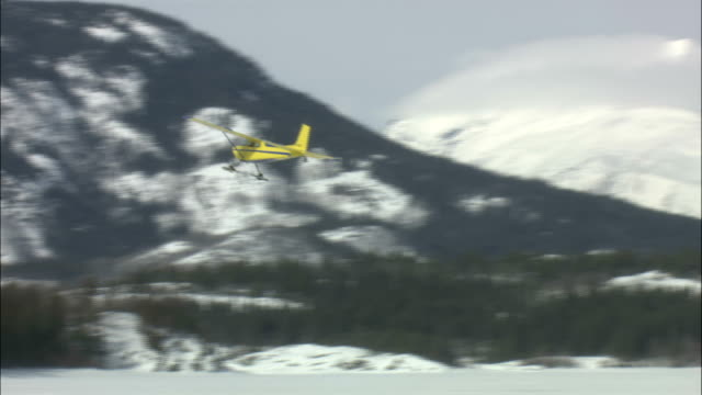 an airplane flies above frozen tagish lake in the yukon territory. - whitehorse stock videos and b-roll footage