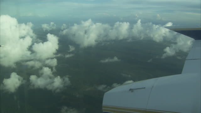 vidéos et rushes de an airplane flies high above the clouds. - aile d'avion