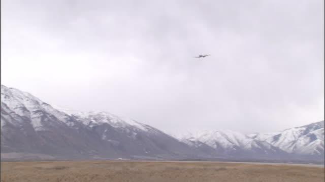 an airplane flies near a snow-capped mountain range. - prairie stock videos & royalty-free footage
