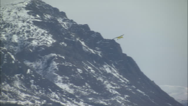 an airplane flies near snowy mountains in the yukon territory. - whitehorse stock videos and b-roll footage