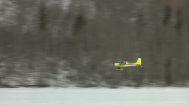 an airplane flies over frozen tagish lake in canada. - whitehorse stock videos and b-roll footage