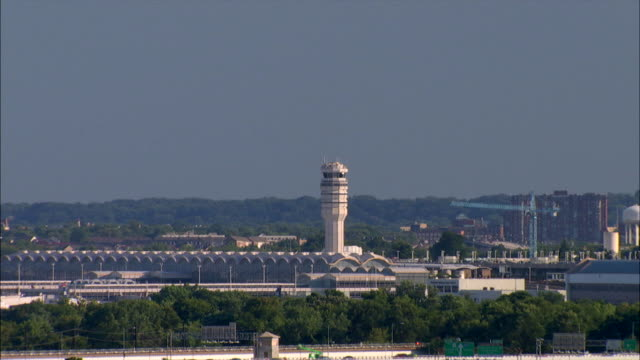 an airplane flies over reagan national airport in washington, dc. - ronald reagan washington national airport stock videos & royalty-free footage