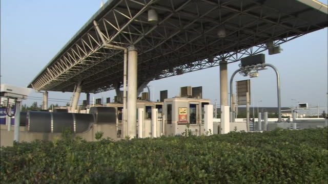 An airplane flies past a toll gate of the access bridge to the airport / Shot on February 2 2009