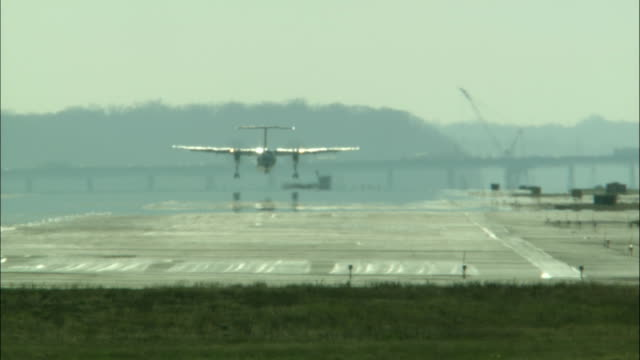an airplane lands on an airport runway. - ronald reagan washington national airport stock videos & royalty-free footage