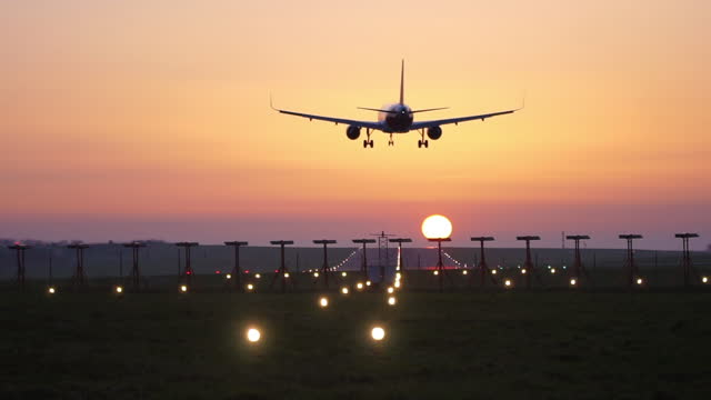 an airplane lowers for landing on airport runway during colorful sunset at bristol airport on may 04 2018, in bristol, united kingdom. - multi coloured stock videos & royalty-free footage
