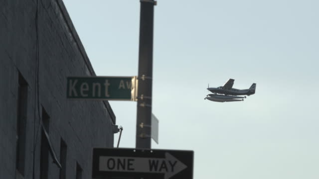 an airplane passes a clear sky in brooklyn, nyc - road sign stock videos & royalty-free footage