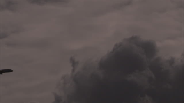 an airplane passes a dark clouds in the sky. - storm cloud stock videos & royalty-free footage