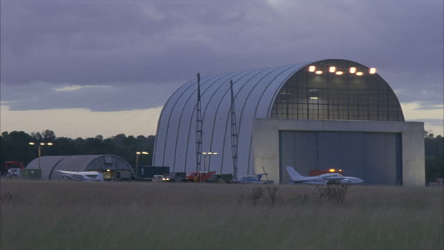 an airplane sits idle outside an airport hangar on an small airfield. - 飛行機格納庫点の映像素材/bロール