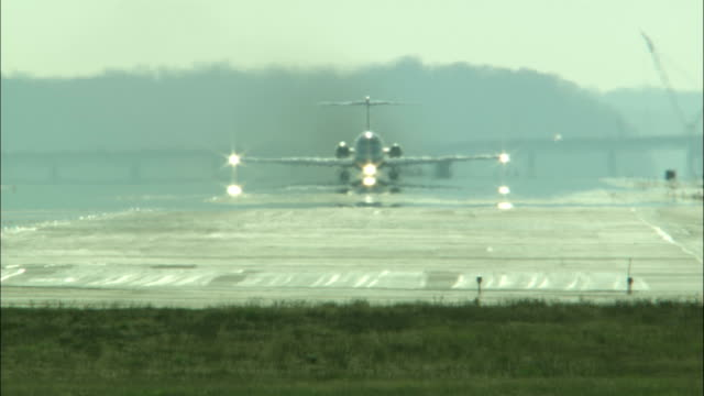an airplane taxis down a runway and takes off. - ロナルド レーガン ワシントン国際空港点の映像素材/bロール