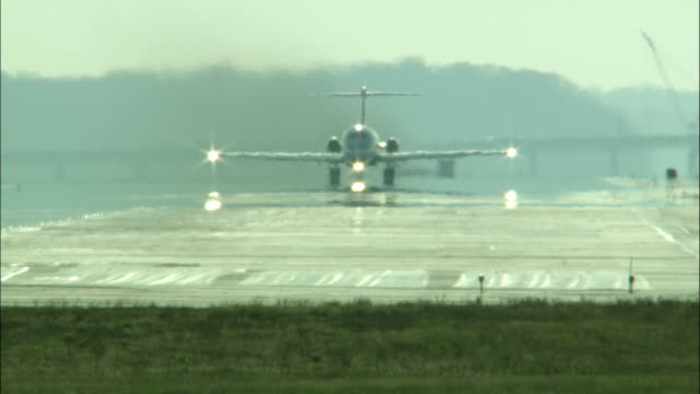 an airplane taxis down a runway and takes off. - aeroporto nazionale di washington ronald reagan video stock e b–roll