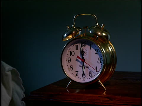 an alarm clock sits on a bedside table. - clock stock videos & royalty-free footage
