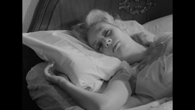 1962 An alarm clock wakes a sleepy woman who rises and dresses into a robe