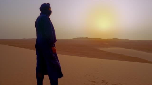 An Algerian man stands in the Sahara Desert under the glowing sun.