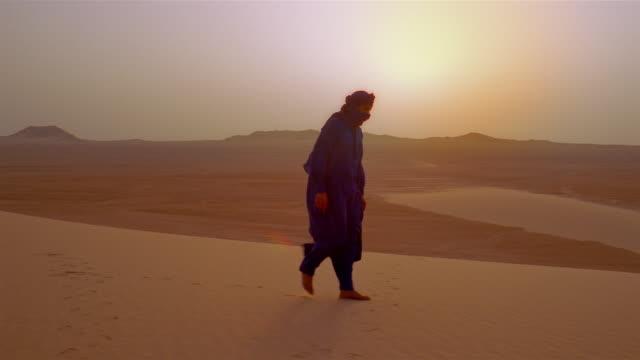 An Algerian man walks in the Sahara Desert under the glowing sun.