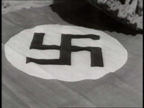 An Allied tank rolls over the Nazi flag as the Allies liberate Belgium during World War II