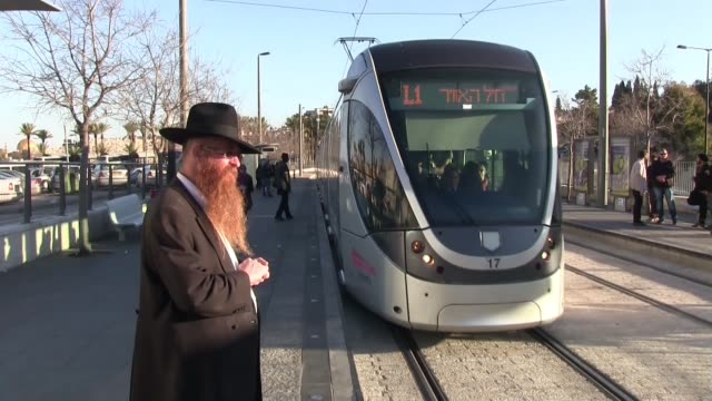 an almost empty light rail tram with smashed windows is viewed as it passes through a volatile east jerusalem on february 24, 2016. even though... - eddie gerald stock videos & royalty-free footage