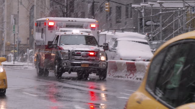 an ambulance drives uptown in a snow storm in new york city. - krise stock-videos und b-roll-filmmaterial