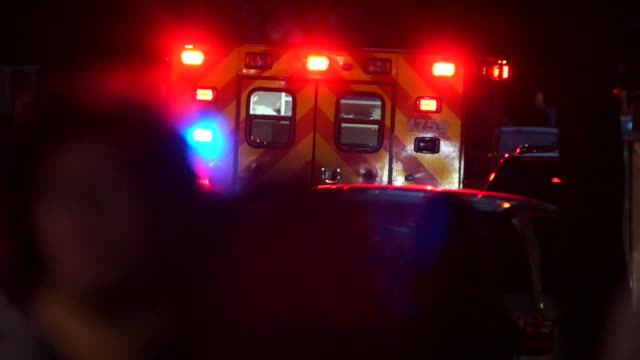 an ambulance is parked with it emergency lights on at night. - ambulance stock videos & royalty-free footage