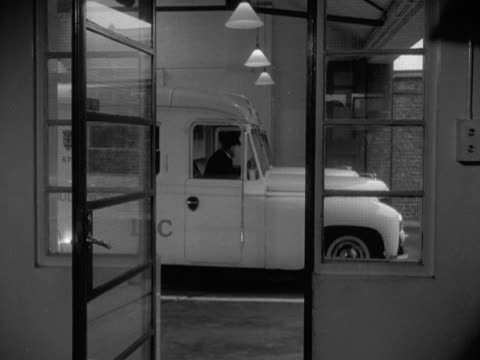 An ambulance man runs out of a control room and into an ambulance as it pulls out of the station 1950's