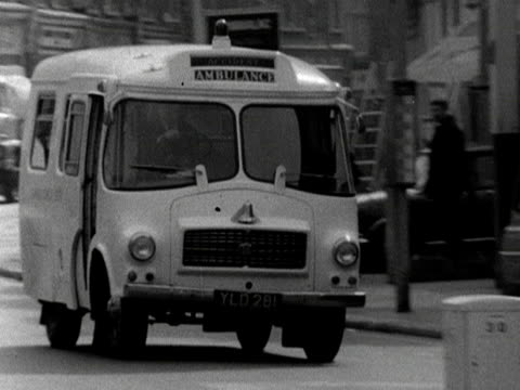 An ambulance moves along a high street and parks up 1968