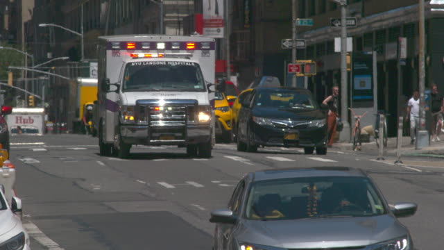 An ambulance navigates New York City Streets and traffic in slow motion on a summer day.