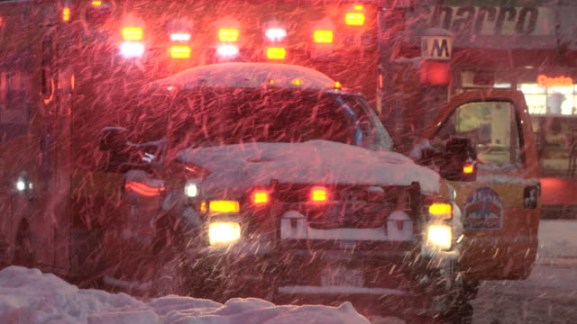 An ambulance parked with its lights on during heavy snowfall in Time Square