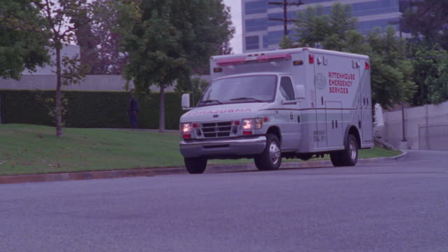 an ambulance passes by a hospital during daytime. - african american ethnicity stock videos & royalty-free footage