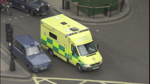 An ambulance passes other traffic and pedestrians in London.