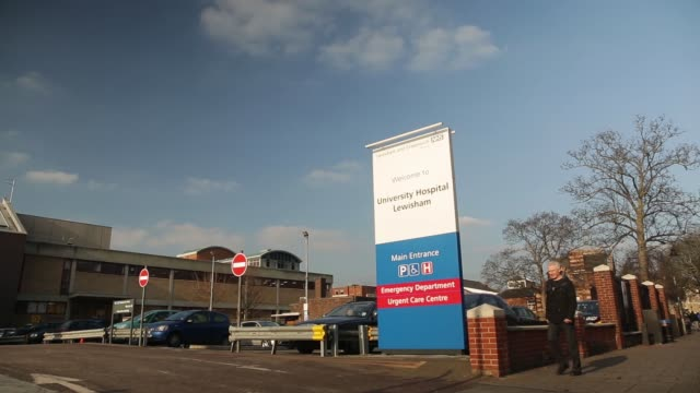 an ambulance passes the sign for the university hospital lewisham in london united kingdom on thursday january 22 gvs of hospital signage - nhs stock videos & royalty-free footage