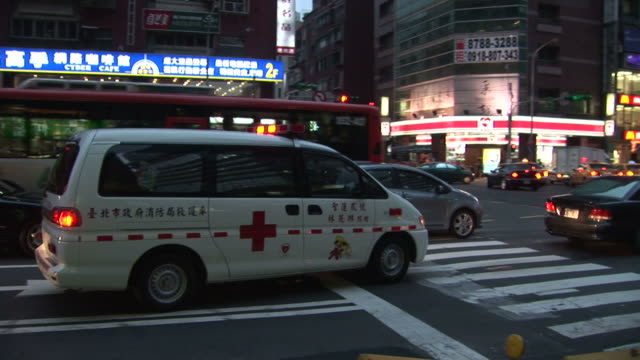 an ambulance passing through the city in taipei taiwan - zebramuster stock-videos und b-roll-filmmaterial