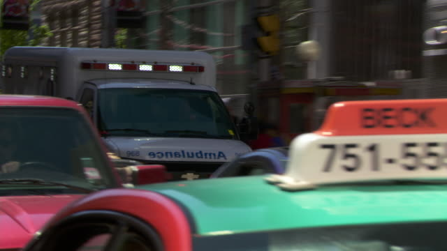 an ambulance rushes up the streets with its lights on queen st in toronto canada - ontario canada stock videos & royalty-free footage