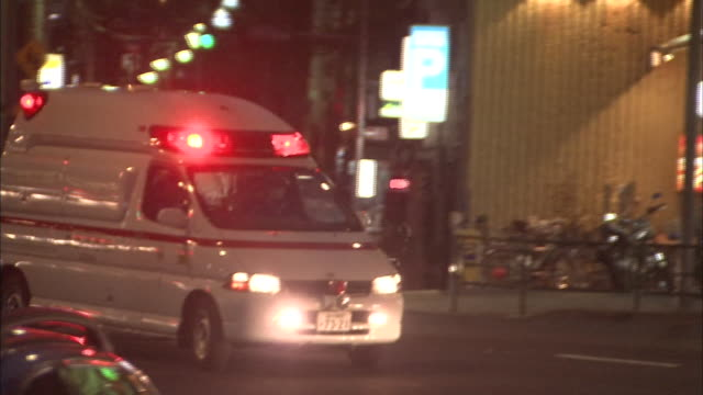 An ambulance uses its emergency lights as it moves on city streets.