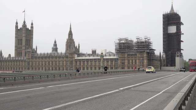 an ambulance vehicle with blues lights flashing and siren sounding rushes towards an emergency over an almost deserted westminster bridge past the... - houses of parliament london stock videos & royalty-free footage