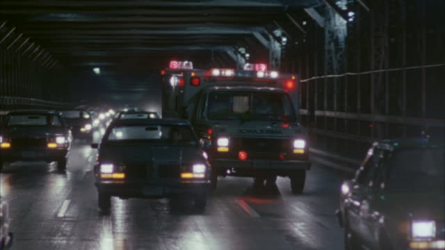 an ambulance weaving in and out of heavy traffic at night. - blaulicht stock-videos und b-roll-filmmaterial
