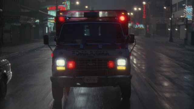 An ambulance with flashing lights drives on a city street.