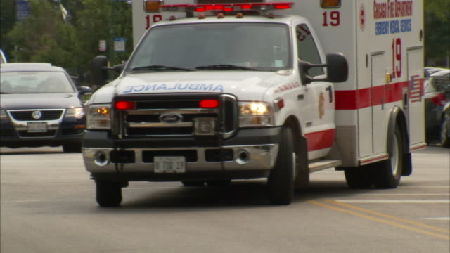 an ambulance with its lights flashing rounds a busy corner. - ambulance stock videos & royalty-free footage